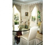 Opulence was a key factor in the client's requirements, which Mimi met without overdoing. The silk-taffeta window treatments were made to follow the curved shape of the windows, instead of commonly going straight across which would have disrupted the symmetry. The striped upholstery in the chairs matched the detailing in the carpet, while the glass table top kept the room from looking too 'heavy'.